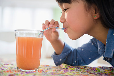 Filipino girl drinking juice on table - p555m1415583 by JGI/Jamie Grill