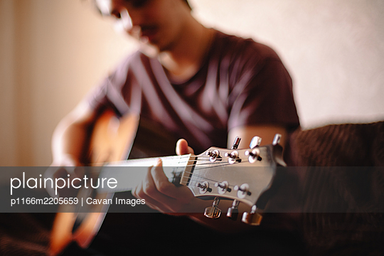 Young man playing guitar at home - p1166m2205659 by Cavan Images