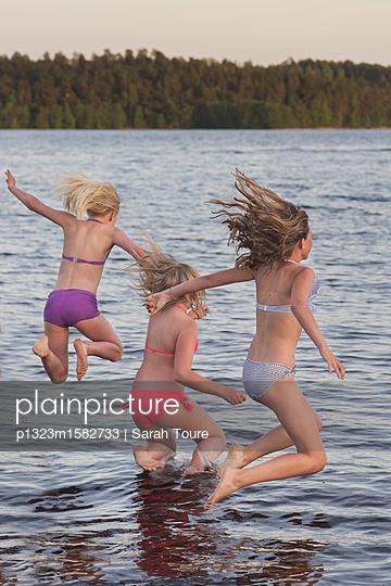 three girls jumping into the water - p1323m1582733 von Sarah Toure