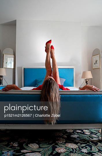 Woman lounging on a bed with her legs in the air - p1521m2126567 by Charlotte Zobel