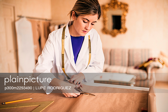 Young female tailor cutting fabric with scissor at workbench - p300m2293490 by LUPE RODRIGUEZ