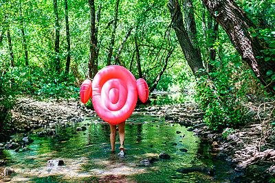 Woman walking in river, carrying an inflatable flamingo - p300m2042126 by Kiko Jimenez