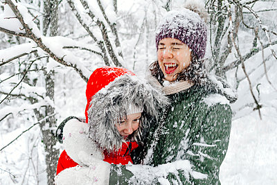 Cheerful teenage girl embracing sister while snowing during vacations - p300m2256345 by Oxana Guryanova