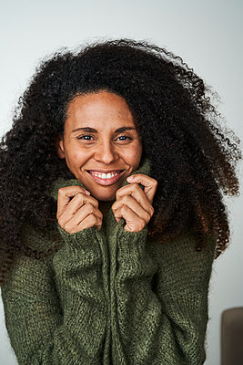 Curly haired woman in sweater against gray background - p300m2264672 by Annika List