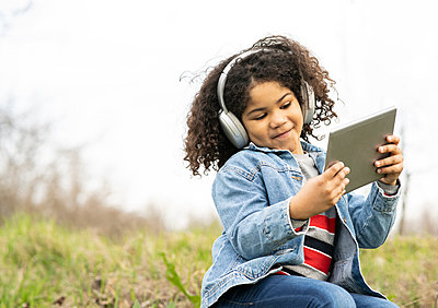 Cute boy listening music through headphones while using digital tablet in nature - p300m2266366 by Jose Carlos Ichiro