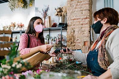 Valencia, Spain. Woman buying flowers in a florist's shop, paying by credit card. - p300m2274234 von Ezequiel Giménez