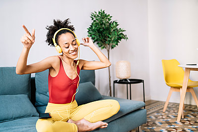 Happy woman listening music while sitting on sofa at home - p300m2275311 by COROIMAGE
