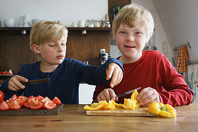 Portrait of disabled boy sitting with brother at table with vegetables in kitchen - p301m1180550 by Halfdark