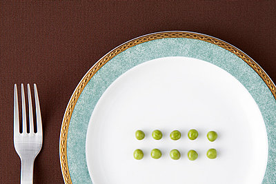 A fork and ten peas arranged neatly on a plate - p5147019f by Opus photography