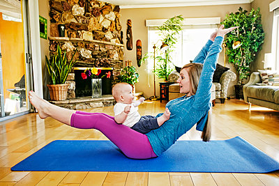 Mother working out on exercise mat with baby in lap - p555m1305280 by Peathegee Inc