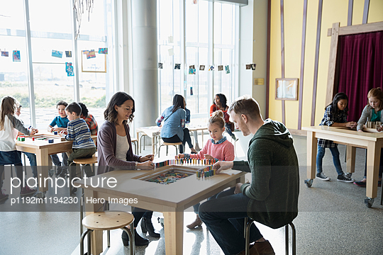 Family playing with dominoes in science center - p1192m1194230 by Hero Images