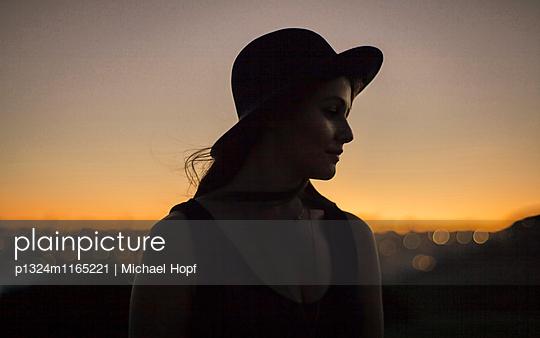Junge Frau mit Hut im Sonnenuntergang - p1324m1165221 von michaelhopf