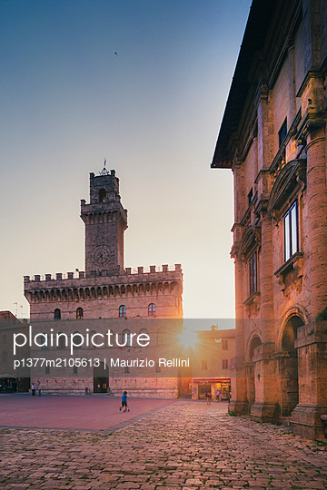 Italy, Tuscany, Siena district, Val di Chiana, Montepulciano, Sun setting beyond the medieval buildings in Piazza Grande square in Montepulciano - p1377m2105613 by Maurizio Rellini