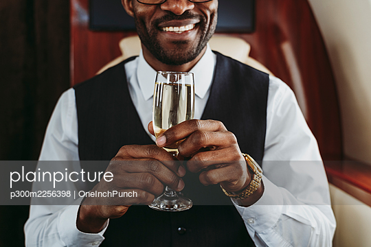 Smiling businessman holding champagne in private jet - p300m2256398 by OneInchPunch