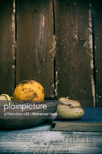 Alte Früchte und altes Buch auf einem Tisch - p794m2031125 von Mohamad Itani