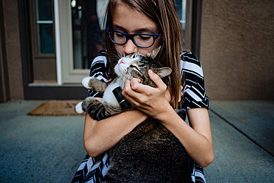 a pre teen girl kissing her cat on the front porch - p1166m2208022 by Cavan Images