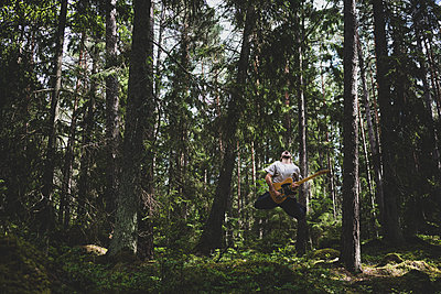 Man playing guitar in the forest - p1295m2133330 by Katharina Bauer