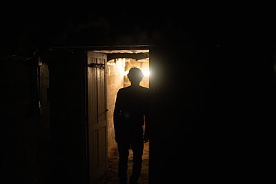 Male silhouette in the basement - p1321m2278385 by Gordon Spooner
