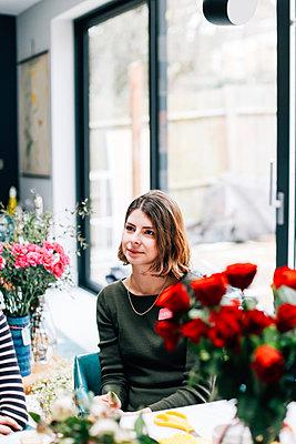 Female student florist listening at flower arranging workshop - p429m1418096 by Alys Tomlinson