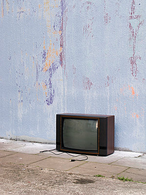 Old television at house wall - p4902765 by Jan Mammey
