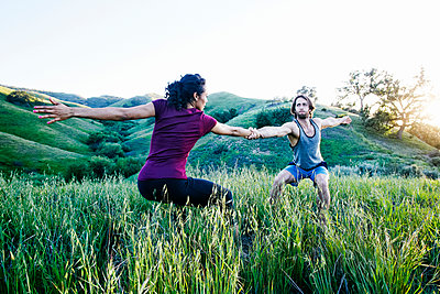 Couple holding hands and practicing yoga on hill - p555m1303370 by Peathegee Inc
