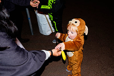 Woman giving treats to Caucasian boy wearing a bear costume - p555m1523134 by Roberto Westbrook