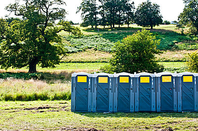 Row of portable toilets in field - p9241926 by Liam Bailey