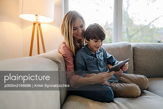 Mother and son sitting on couch, using digital tablet - p300m2166686 von Kniel Synnatzschke