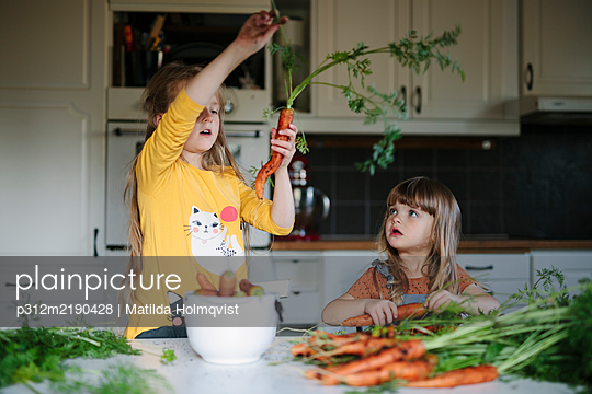 Sisters in kitchen - p312m2190428 by Matilda Holmqvist