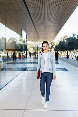 Attractive young woman walking with laptop by corporate building - p1166m2095879 by Cavan Images