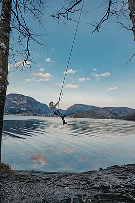 Young man on a swing next to Bohinj Lake in Slovenia - p1455m2077125 by Ingmar Wein