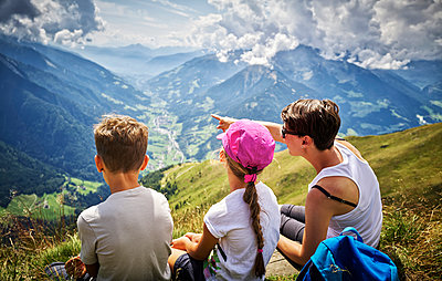 Mother with two children having a break from hiking in alpine scenery, Passeier Valley, South Tyrol, Italy - p300m2154743 by Dirk Kittelberger