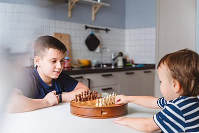 Siblings playing chess at dining table in kitchen at home - p300m2276726 by Katharina und Ekaterina