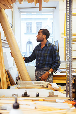Confident young craftsman looking at timber standing in framing workshop - p426m2089071 by Maskot