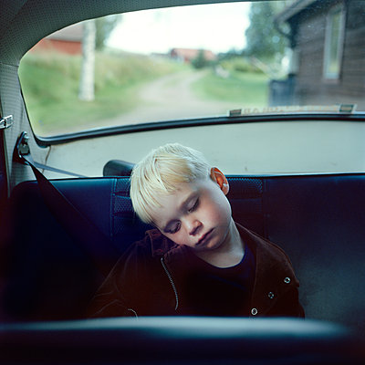 Boy sleeping on back seat of car - p528m1075415f by Johan Willner