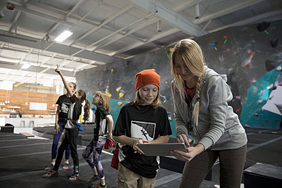 Female instructor with clipboard teaching boy rock climber student at climbing wall in climbing gym - p1192m1560053 by Hero Images
