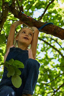 Girl wearing daisy flower wreath climbing in a tree - p300m2198608 by Maya Claussen