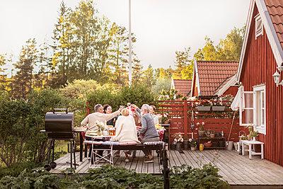 Family having meal in garden - p312m2208123 by Plattform
