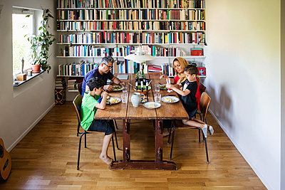 Family having meal at dining table by bookshelf - p426m1193047 by Maskot