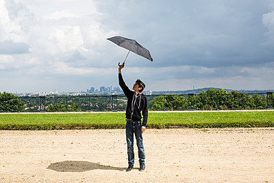 Teen playing with an umbrella - p445m1153165 by Marie Docher