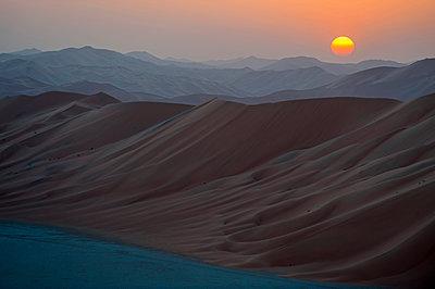 Middle East, Oman.  Dunes of  The Empty Quarter or Ar Rub al Khali at sunset. - p652m1576201 by John Warburton-Lee