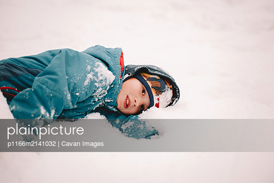Thoughtful boy lying in snow during winter - p1166m2141032 by Cavan Images