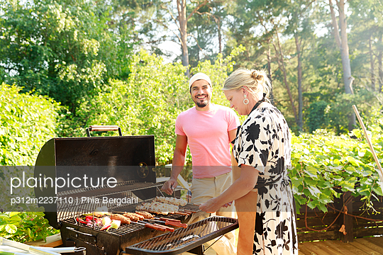 Couple having barbecue in garden - p312m2237110 by Phia Bergdahl