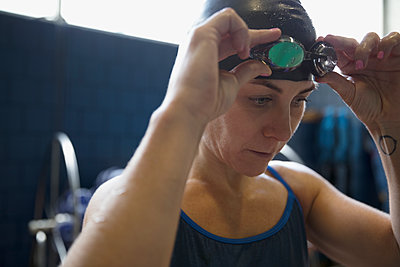 Close up serious female swimmer adjusting swimming goggles - p1192m1447616 by Hero Images