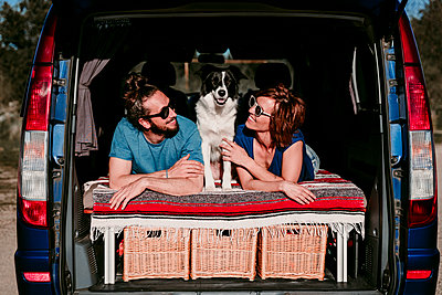 Relaxed couple with dog lying in the boot of a minivan - p300m2198024 by Eva Blanco