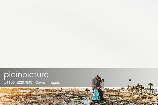 Family hug at beach: mid-40's parents 12 yr old boy and 8 yr old girl - p1166m2207843 by Cavan Images