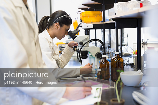 Scientist using microscope in laboratory - p1192m1145640 by Hero Images