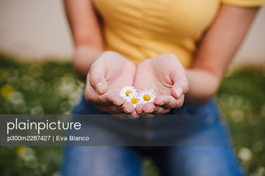 Woman holding flowers in hands - p300m2287427 by Eva Blanco