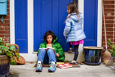 A young boy sits on his front stoop with his sister reading - p1166m2073785 by Cavan Images