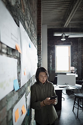 Creative businessman texting with smart phone, brainstorming in office - p1192m1447559 by Hero Images